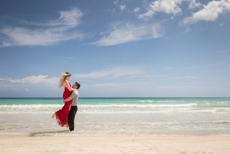 Bride lifted by groom on the beach