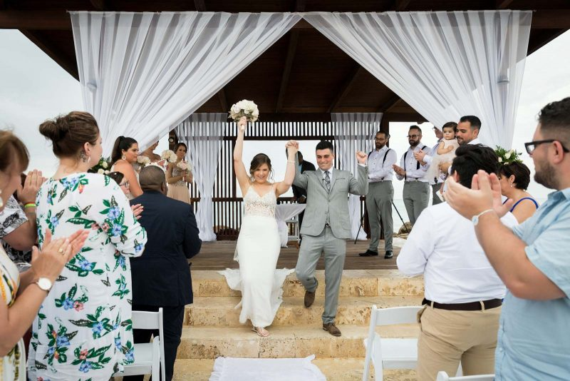 Newlyweds hands in the air after ceremony