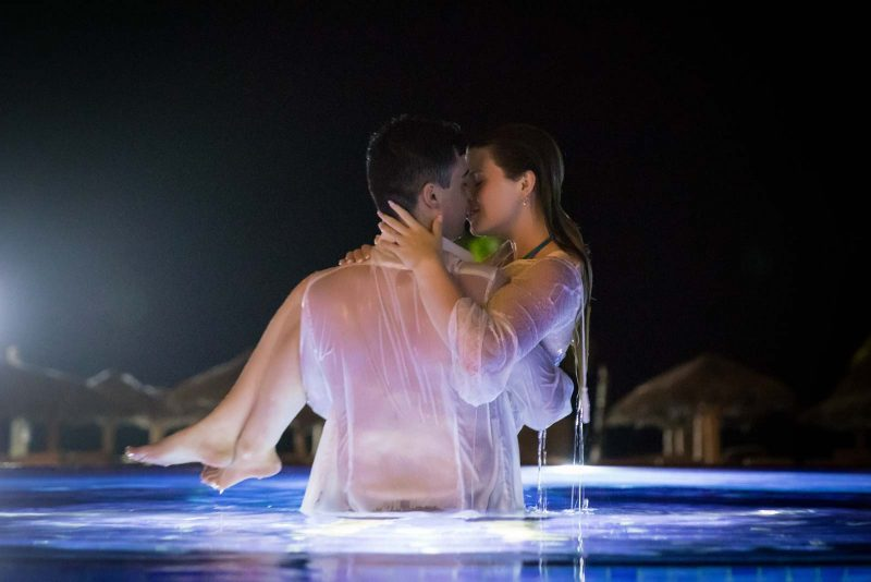 Groom holding up bride in swimming pool at night