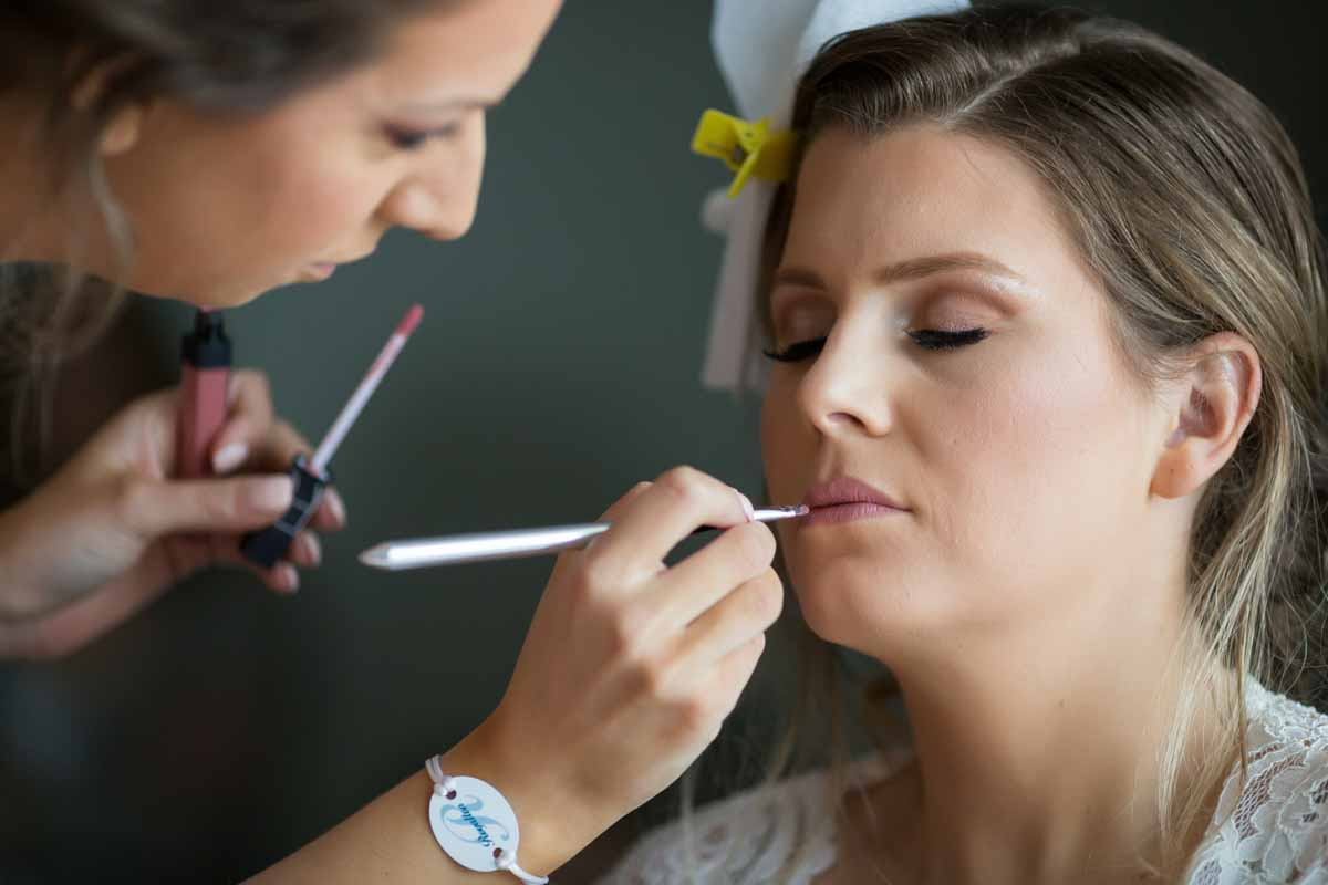 Bride getting lip gloss during preparation