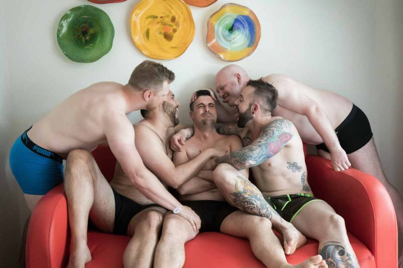Groomsmen wearing boxers laughing during preparation