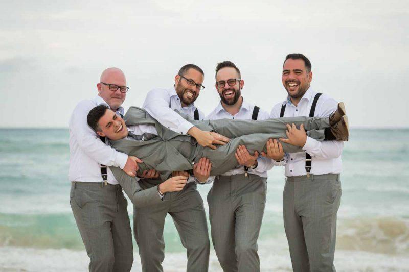 Groomsmen lifting up groom