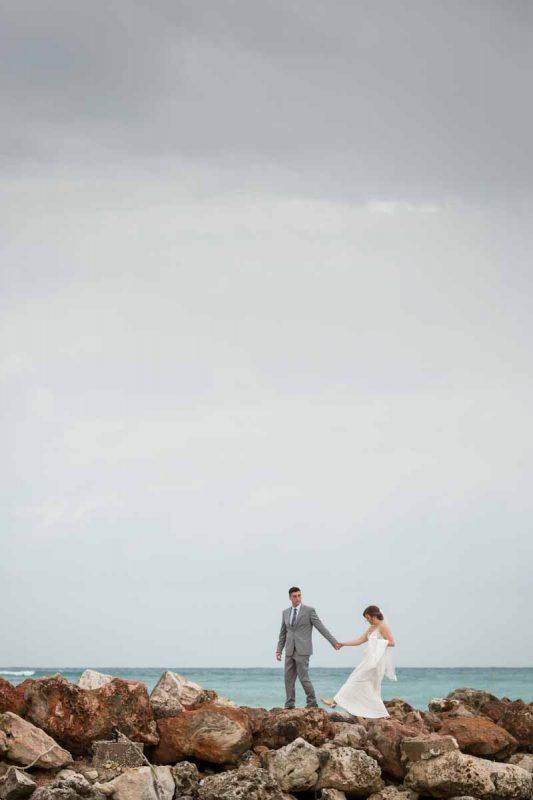 Newlyweds walking on rocks Royalton White Sands