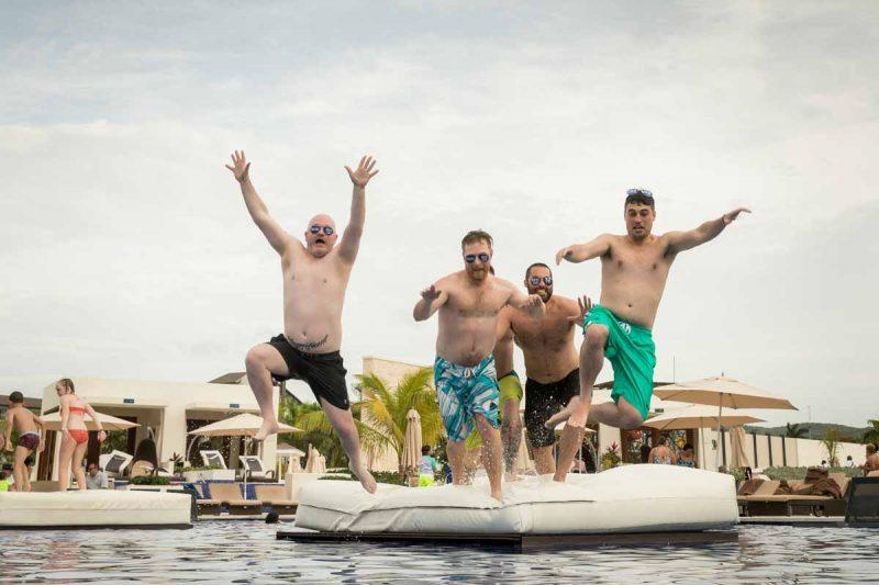 Groomsmen jumping into swimming pool