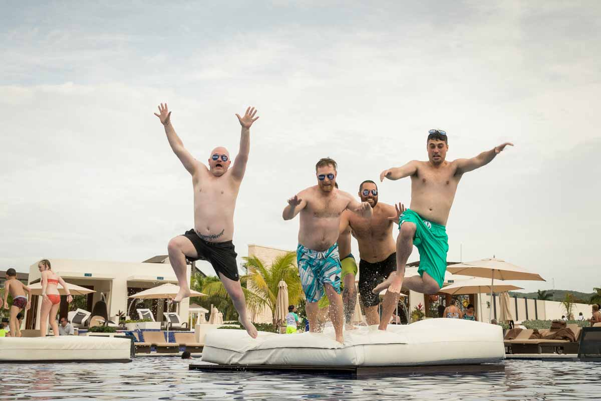 Groomsmen jumping into swimming pool