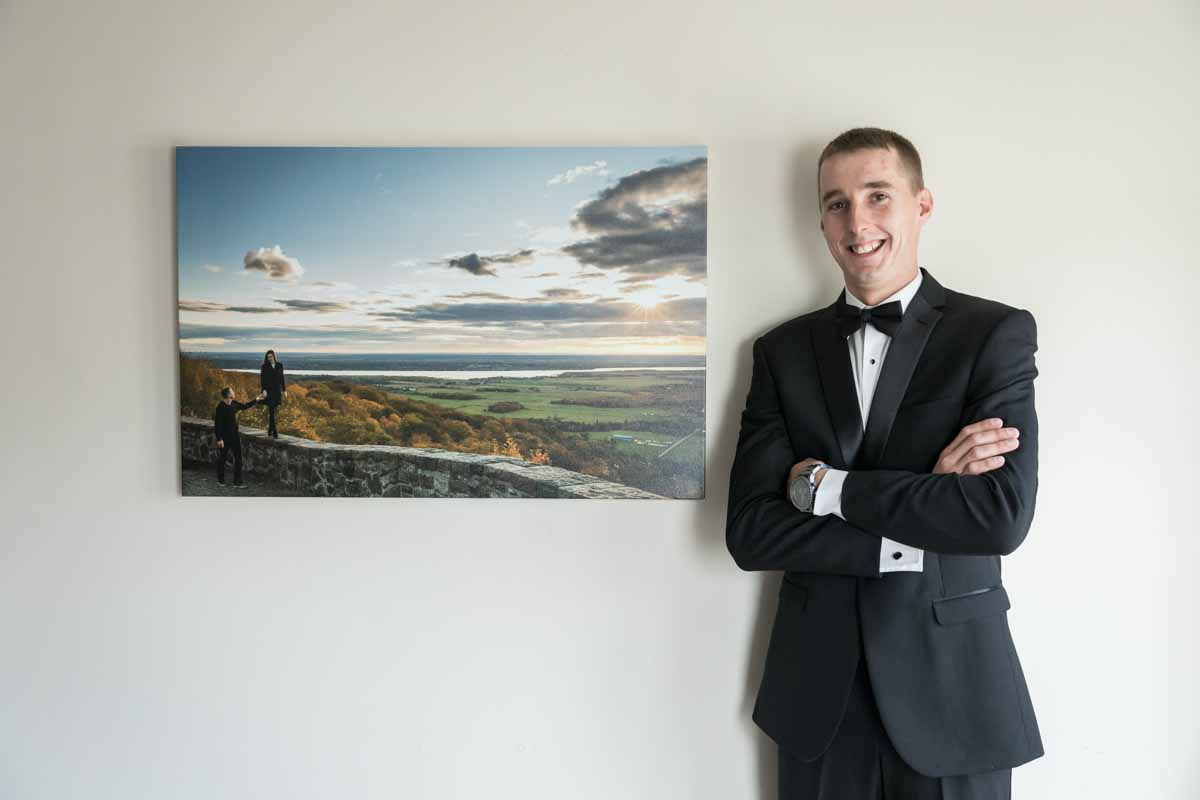 Groom posing next to own photo