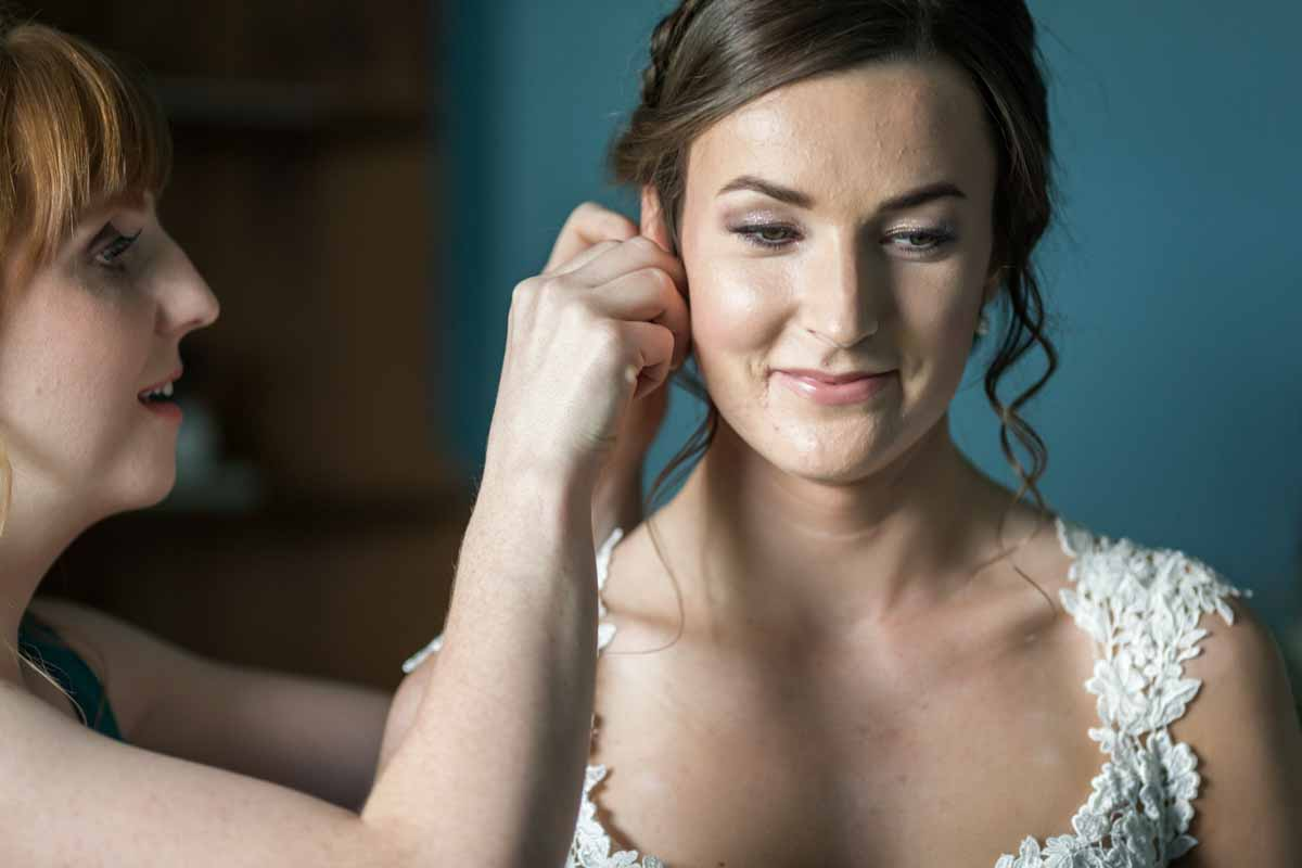 Bridesmaid putting on earrings