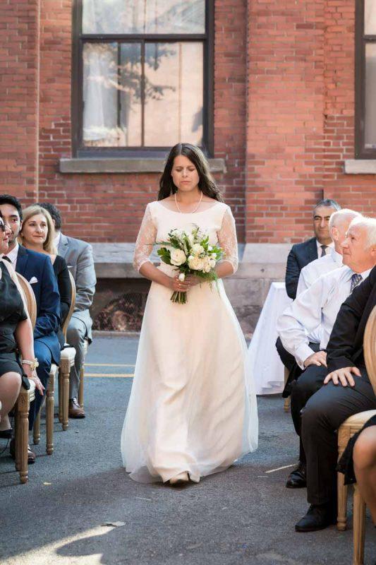 Bride walking into ceremony at Entrepots Dominion