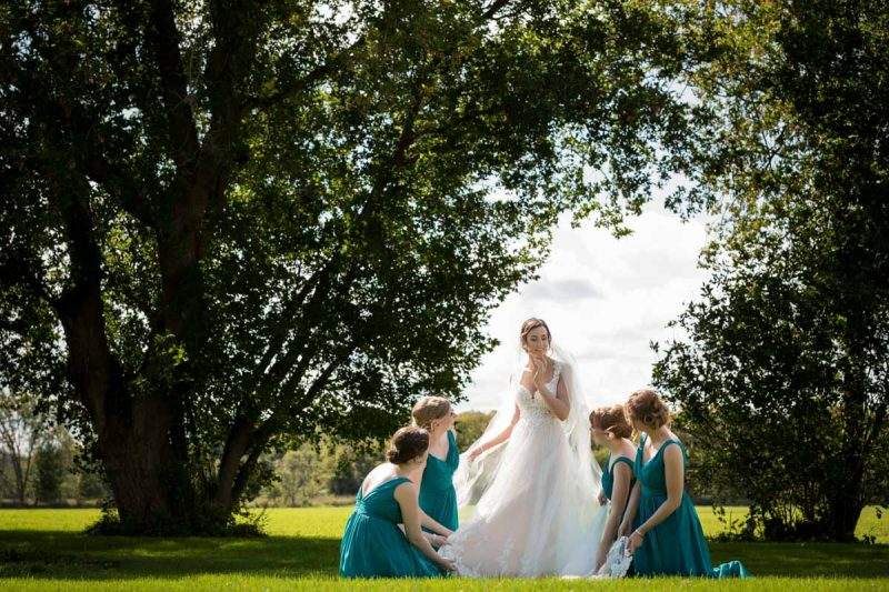 Bridesmaids lifting bride's dress